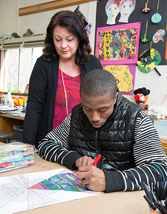 African Amercan male student wokign with teacher at Bergen Center for Child Development - private special education school in Haworth NJ